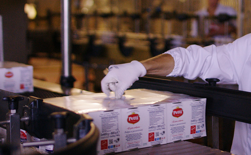 A worker manually attaches particular labels to products in the packaging phase of the cluster
