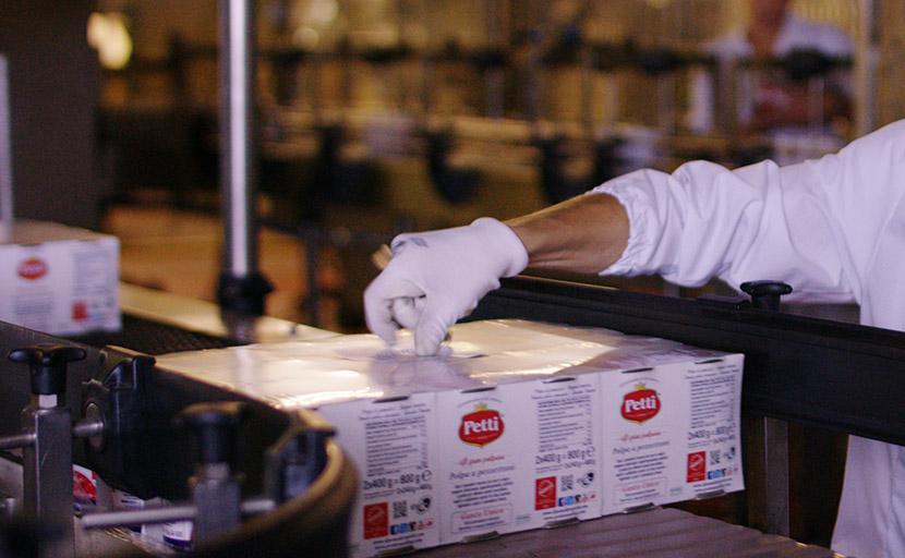 Un'operaia attacca manualmente le etichette ai prodotti Petti nella fase di confezionamento dei cluster nello stabilimento dell'Italian Food S.p.A. a Venturina Terme