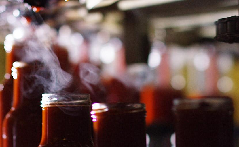 Dettaglio del riempimento automatico delle bottiglie attraverso la macchina riempitrice nello stabilimento dell'Italian Food S.p.A. - Petti