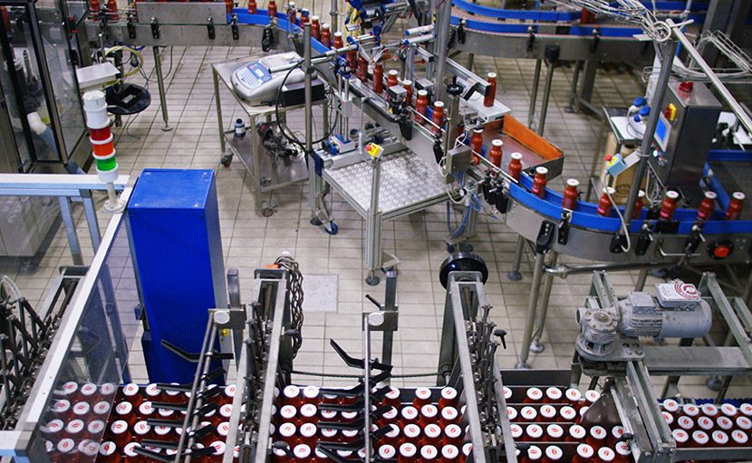View from the top of the line labeling and packaging of the bottles of tomato sauce.